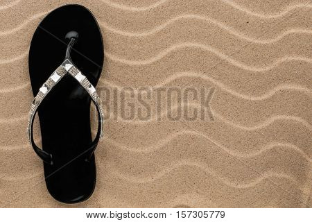 Black flip flops with rhinestones on the wavy sand. With place for your text