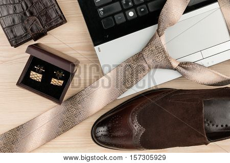 Fashion and business notebook shoes cufflinks and tie on a wooden table as background. View from above