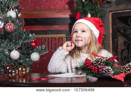 Christmas Child Write Letter to Santa Claus, Kid in Santa Hat Writing Wish List.