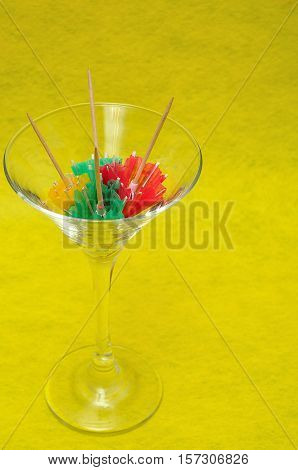 A martini glass filled with cocktail umbrellas
