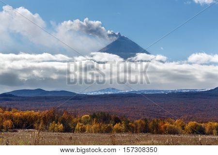 Beautiful view of explosive-effusive eruption of Klyuchevskaya Sopka (Klyuchevskoy Volcano): powerful plume of gas steam ash from crater volcano. Picturesque view of volcanic eruption on sunny day.