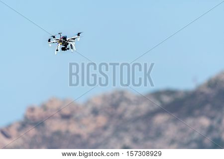 Drone with camera hovering over mountains. Flying drone with camera.