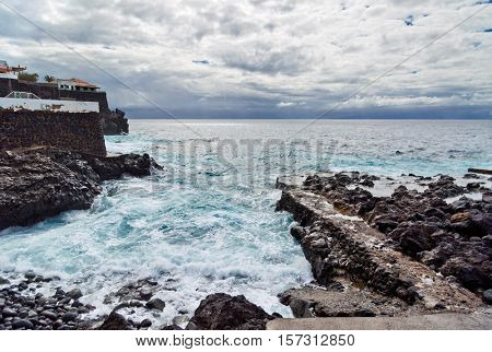 Black stones beach beach in cloudy gloomy weather. Tenerife island. Spain