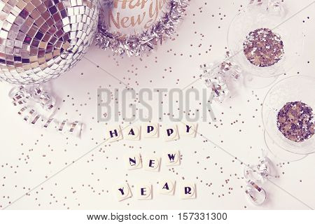 Over head flat lay view of a chic white and silver New Years Eve concept. Party hat, disco ball and glasses filled with silver confetti.