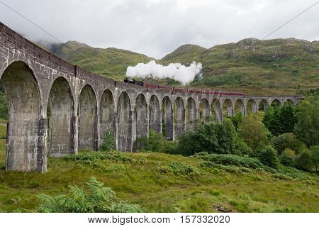 Train crosses the Glenfinnan railway viaduct in the Western Highlands of Scotland