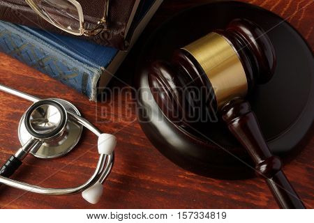 Medical error concept. Stethoscope and gavel on a table.