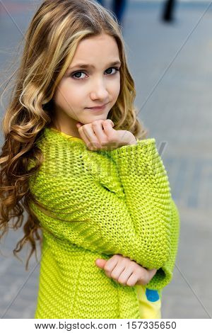portrait of a beautiful blonde girl in a green cardigan