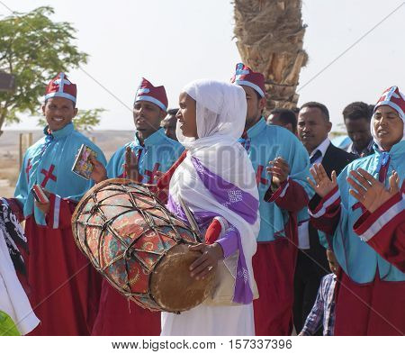 JERICHO, ISRAEL - NOV 12, 2016: Unidentified woman in national clothes playing drum during pilgrimage at Qasr el-Yahud the Baptismal site on Jordan river.