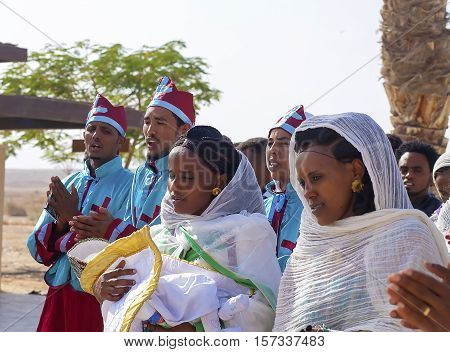 JERICHO, ISRAEL - NOV 12, 2016: Ethiopian pilgrims in celebration clothes sing while visiting Qasr el Yahud the Baptismal site on Jordan river.