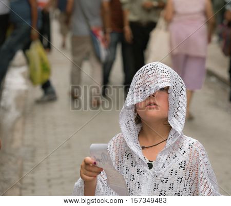 beautiful lonely little girl standing on the street and holding piece of paper in her hand