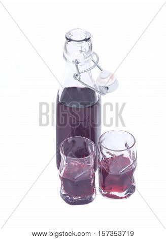 Homemade raspberry liqueur in clear glass bottle with swing top and shot glass isolated on white background