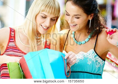 Portrait of two stylish women looking into paperbag with new clothes in shop