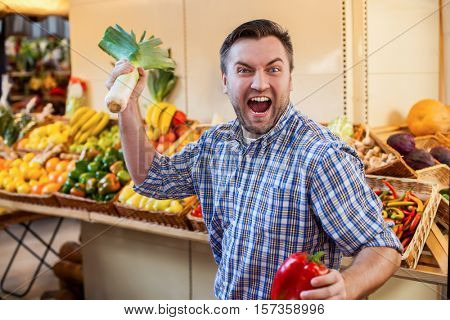 Man jokes with leek and red pepper in hands.