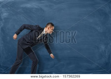 Businessman standing as if he is going to run or pursue his goal on the blue chalkboard background. Beginning of one's career. Face up to difficulties. Ready to chase success and profit.