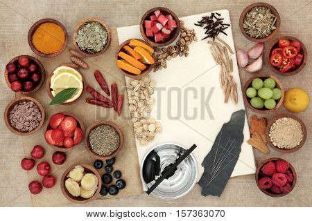 Alternative medicine for cold remedy with acupuncture needles and moxa sticks and fresh and dried food on hemp notebook background. High in antioxidants, anthocyanns minerals and vitamins.