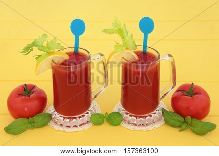 Tomato juice health drinks with lemon, celery and basil herb over yellow wood background. High in vitamins, anthocyanins and antioxidants.