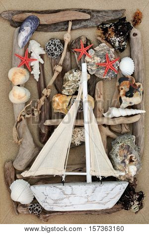 Decorative sailing boat on abstract background with seashells, driftwood, rocks and seaweed on sand.