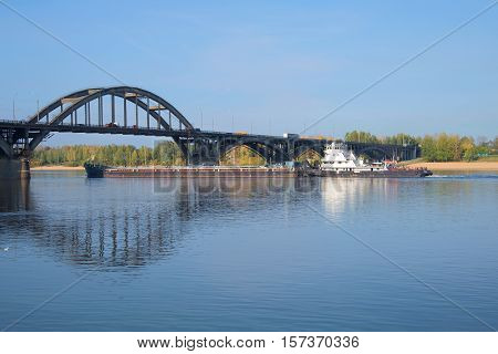 RYBINSK, RUSSIA - SEPTEMBER 26, 2015: River tug OT-2078 with a barge passes the bridge on the river Volga