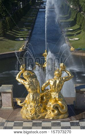 SAINT PETERSBURG, RUSSIA - JULY 03, 2015: Two of Triton blowing shells over a Large sea channel. Fragment of the Grand cascade, The historical landmark of the Peterhof