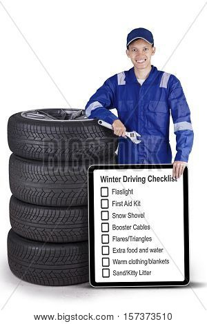 Picture of an Asian mechanic holding wrench and tips on driving in winter on the board while leaning with a pile of tyres in the studio