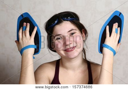 teenager professional swimmer girl in swimming suit with water glasses and paddles close up smiling portrait