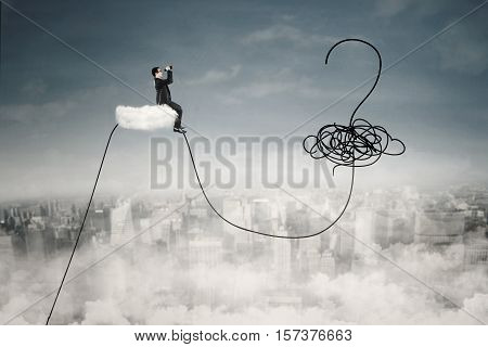 Young businessman sitting on the cloud and looking at a question mark at the sky