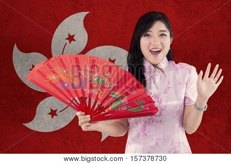 Picture of cheerful Chinese woman holding a fan while wearing cheongsam dress with flag of Hong Kong