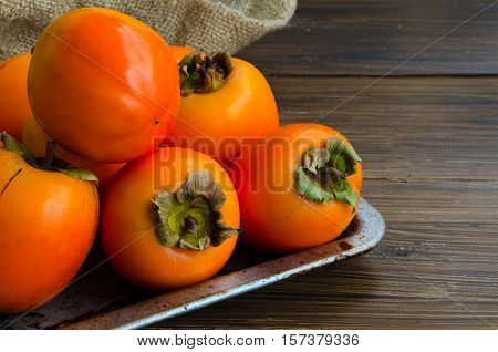 Fresh organic persimmon in vintage metal plate on rustic wood background. Concept for healthy food vegan or raw diet.Copy space.