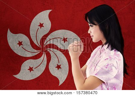 Portrait of beautiful woman wearing cheongsam dress congratulate Chinese new year with flag of Hong Kong