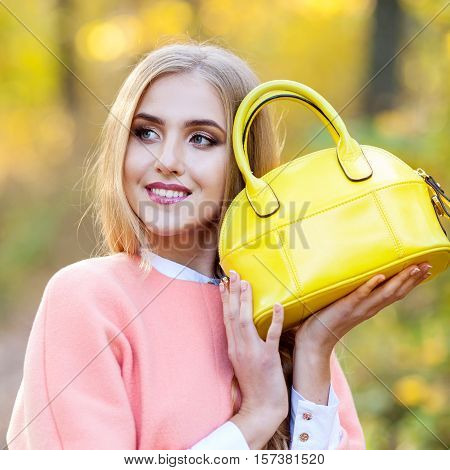 Beautiful girl with a smile and long hair coat is holding a yellow bag fashion autumn day in nature