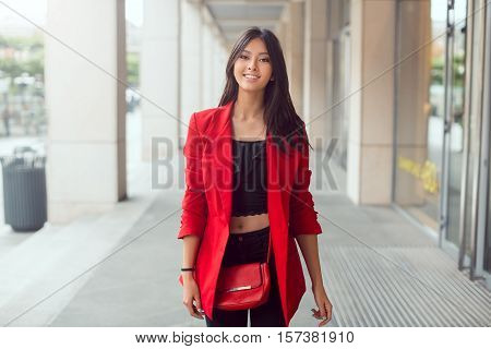 Happy asian woman walking outdoors in business casual red suite against mall and looking at camera