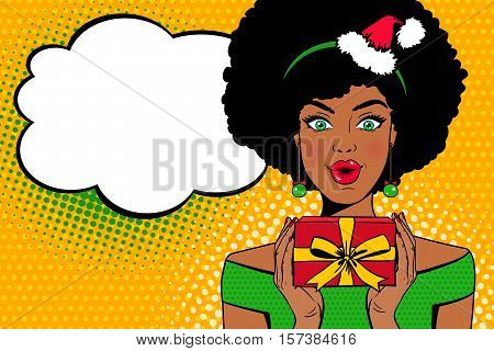 Pop art face. Sexy afro american woman with open mouth in Santa Claus hat holding a gift box in her hands and speech bubble. Vector Christmas background in pop art retro comic style. Party invitation.