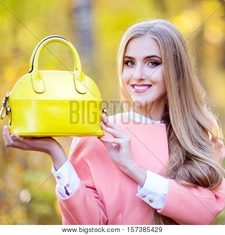 Fashionable stylish young woman with long thick hair in an autumn coat with a yellow leather bag in hand on nature autumn day