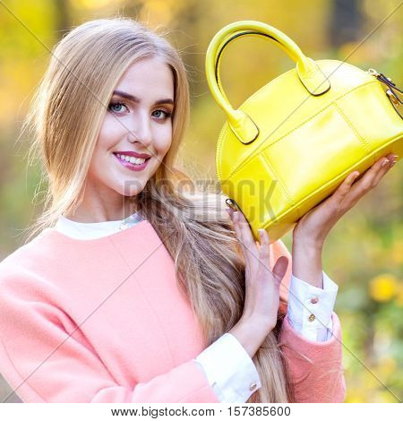 Portrait of a beautiful young woman in a pink coat and a yellow bag in the hands of an autumn day in the park