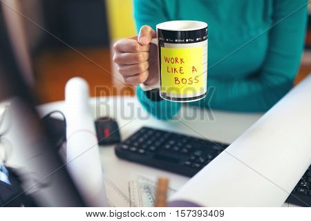 Woman holding a cup of coffee with a motivational message: Work like a boss!