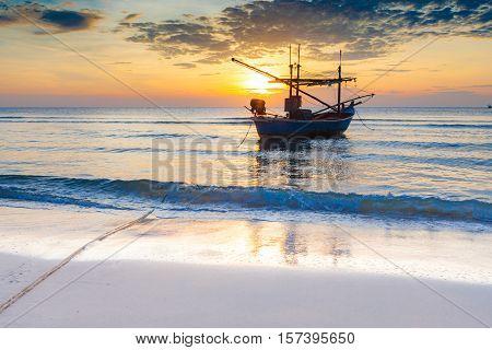 An impressive sunrise over the sea with boats at Hua Hin beach Thailand.