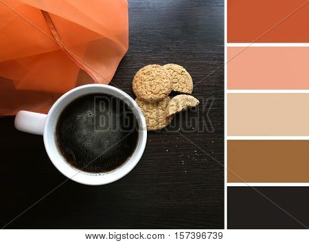 Cup with hot coffee on wooden table and palette of colors