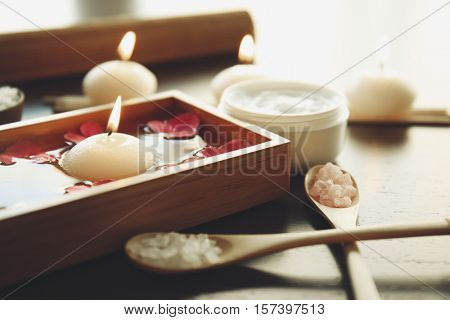Spa set with nutrient cream, sea salt in spoons and candles on wooden background