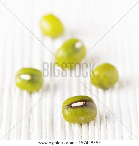 Five green mung beans on white wood.