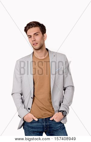 the young guy in a jacket and jeans looks in the camera