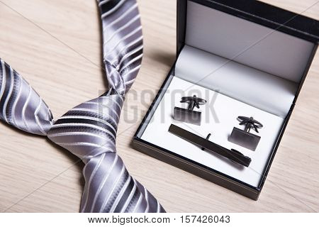 Tie And Cufflinks On Wooden Table