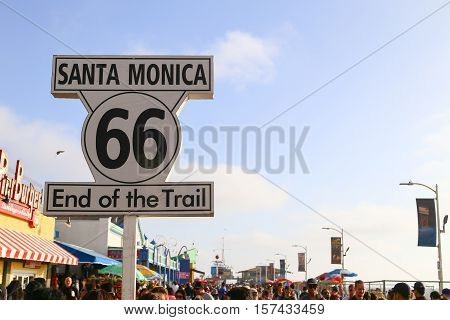 SANTA MONICA, USA - MAY 30, 2015: Sign marking the end of the Route 66 on the crowded Santa Monica Pier.