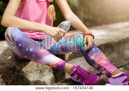 Athlete Girl Sitting On Curb And Drinking Water Out Of Plastic Bottle During Cardio Workout Break. F