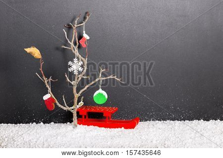 Bare Tree With Leaf, Mittens, Boot, Snowflake, Christmas Ball And Red Festive Sled In Snow On Chalkb