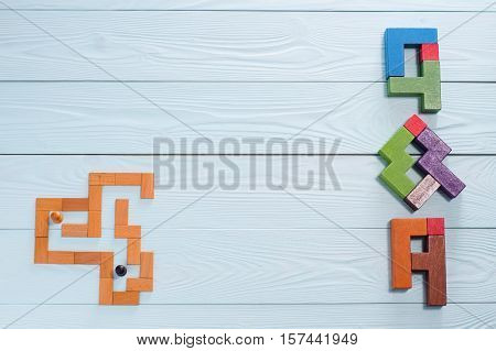 Concept search Answer: the man in the maze and letters Q & A made from wooden blocks top view flat lay. Questions and Answers on a wooden background with copy space.