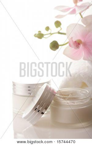 olla de hidratante crema de cara y hermosas flores de orquídeas