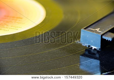 Closeup of old and dusty vinyl record player with arm and needle in focus