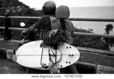 Father with the daughter ride by motorcycle with surfing boards to the beach. Black-white photo.