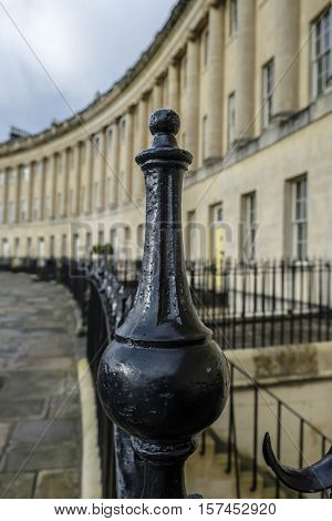 Selective focus on black wrought iron railings with the sweep of grand Georgian architecture of Royal Crescent Bath England in background portrait format