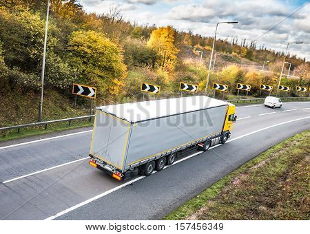 Yellow lorry in motion on the road in autumn scenery